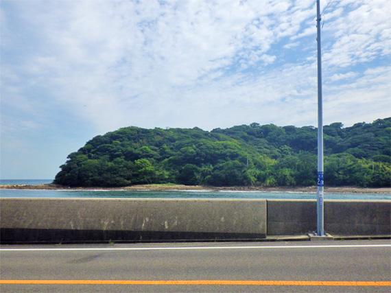 淡路島の由良港付近の風景。道路の向こうには海が川のように狭くなっている「水道」があり、その先に離島「成ヶ島」が見える。