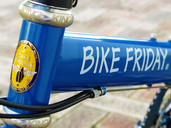 バイクフライデーの折り畳みミニベロ「ニューワールドツーリスト」のメインフレームを斜め前から見た写真。美しい青色の塗装に、白いアルファベットで「BIKEFRIDAY」の文字のステッカーが貼られている。