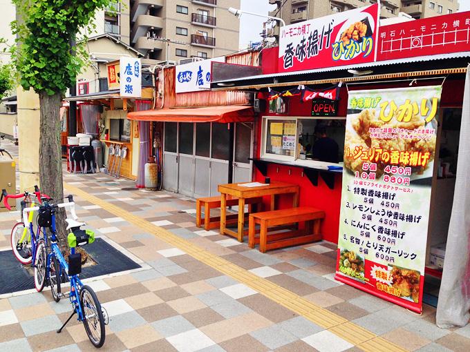 いくつもの小さな飲食店が並んでいて、一番手前のお店は真っ赤な壁で、看板には唐揚げの写真が付いている。「香味揚げ