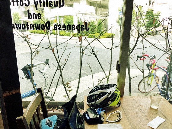 大阪の南堀江にある飲食店「エンジョイ・カフェ」の店内、窓辺の席から外を眺めた写真。窓の外には2台の自転車「ニューワールドツーリスト」と「コメットR」が停められているのが見える。