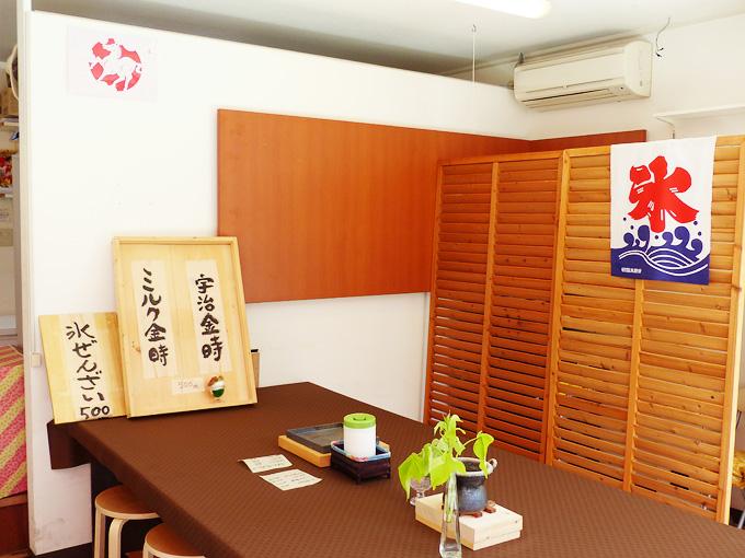 神戸の須磨寺商店街にある和菓子屋さん「神戸天ペロ」の店内の写真。木製の壁には「氷」の文字が書かれた「かき氷」ののぼりが吊るしてあり、テーブルには宇治金時やミルク金時など「かき氷」のメニューが置かれている。