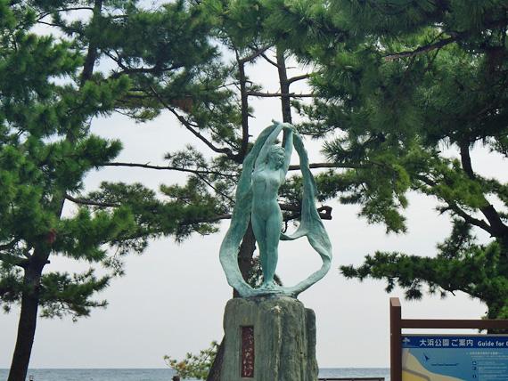 人の形をした青銅色の銅像の拡大写真。女性像のようであるが奇妙な形をしている。