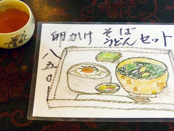 「はんじ」のテーブルメニューを写した写真。「玉子かけ、そば・うどんセット」のメニューで、お料理が手描きのイラストで描かれている。