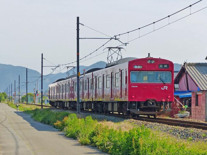 田園風景を通る単線の線路をJR播但線の赤い電車が走ってゆく写真。