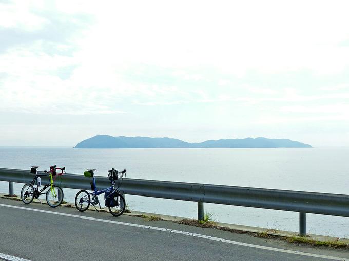 高台から海を見下ろす風景。海の向こうには「沼島」が見える。ガードレールの前に2台の自転車、バイクフライデーの折り畳みミニベロ「ニューワールドツーリスト」とミニベロロード「コメットR」が停められている。