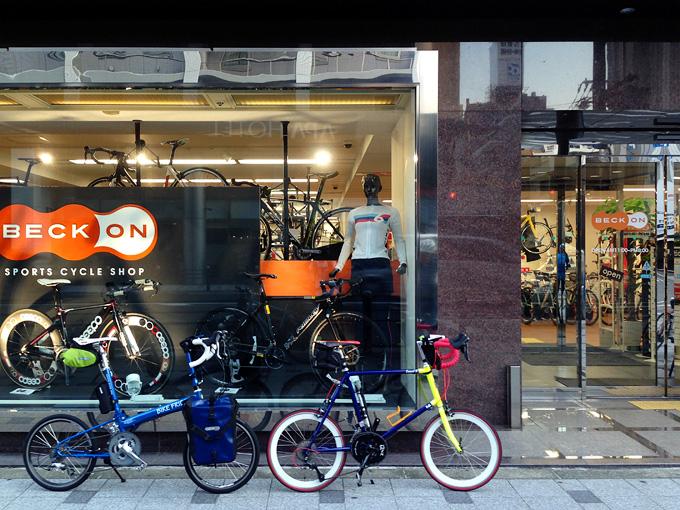 大阪にある自転車店「ベックオン」の店舗前の写真。ショーウィンドウの前にバイクフライデーの折り畳みミニベロ「ニューワールドツーリスト」と友人の自転車「コメットR」が停められている。