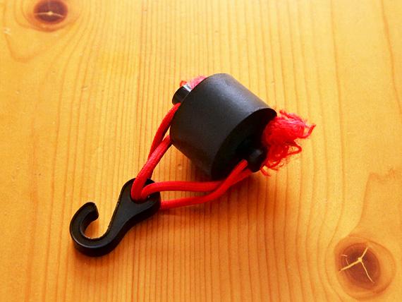 黒いゴム製の車輪のような形のものに、パイプが貫通して、バンジーコードとフックが付けられた保護具の写真。