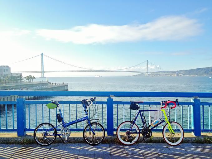 兵庫県明石市の大蔵海岸付近の、朝霧川にかかる橋の上に2台の自転車、バイクフライデーの折り畳みミニベロ「ニューワールドツーリスト」とフジのミニベロロード「コメットR」が停められている写真。背景には海と淡路島、明石海峡大橋が見える。