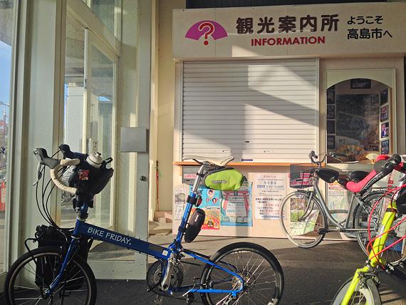 JR「安曇川駅」の構内の写真。「観光案内所」と書かれた窓口の前に2台の自転車、「ニューワールドツーリスト」と「コメットR」が停められている。