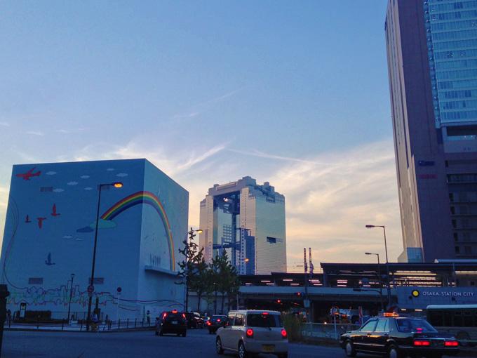 夕暮れ時の大阪駅前の風景の写真。JR大阪駅のホームのむこうに梅田スカイビルが見える。