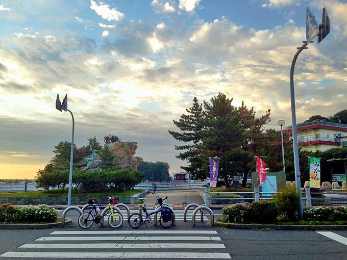 早朝の淡路島・岩屋港付近の写真。道路脇に2台の自転車、バイクフライデーの折り畳みミニベロ「ニューワールドツーリスト」とミニベロロード「コメットR」が停められている。むこうには「絵島」が見える。