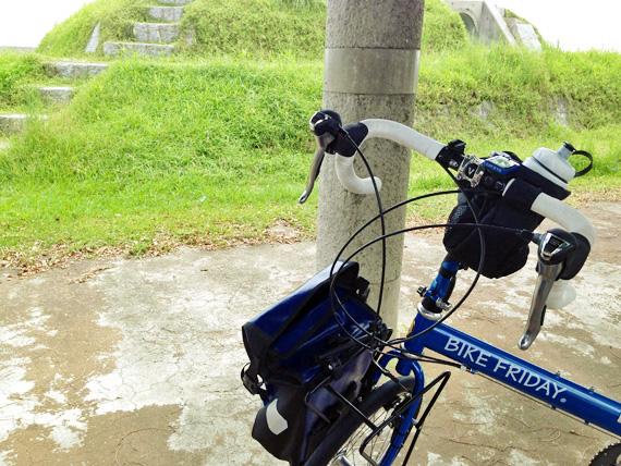 淡路島の南端付近にある「土生港」付近の風景。緑色の草が生い茂る公園の一角に、バイクフライデーの折り畳みミニベロ「ニューワールドツーリスト」が停められている写真。