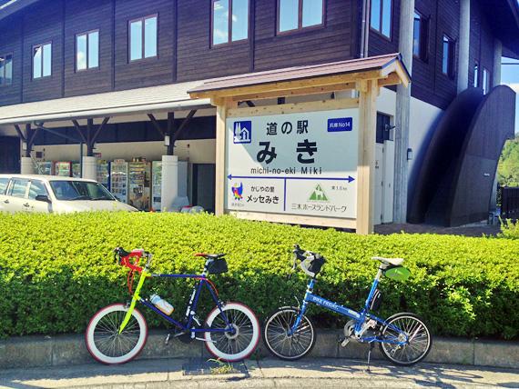 道の駅「みき」と書かれた看板の前に2台の自転車、バイクフライデーの折り畳みミニベロ「ニューワールドツーリスト」とフジのミニベロロード「コメットR」が停められている写真。