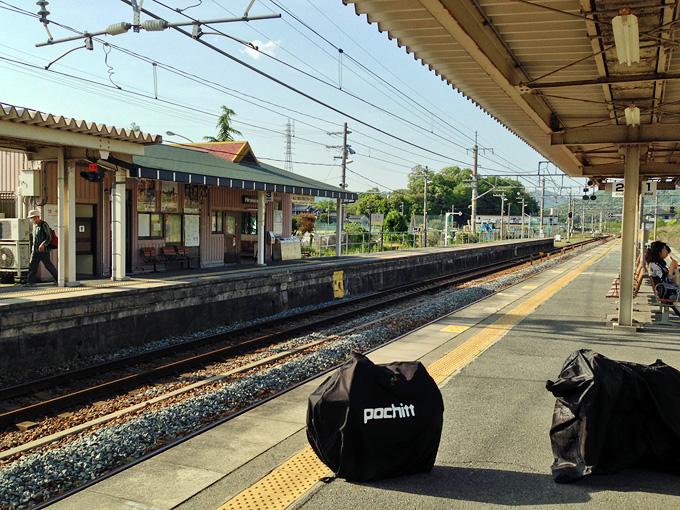 駅のホームに、自転車が入った輪行袋が置かれている写真。