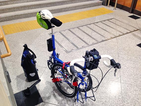JR大阪駅の構内で、バイクフライデーの折り畳みミニベロ「ニューワールドツーリスト」が折り畳み状態から組み立てられている途中の写真。