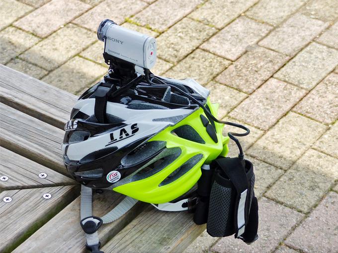 自転車用ヘルメットの後部に、モバイルバッテリーが入った「TNIバイクポケット」が装着されている写真。モバイルバッテリーから出ているUSBケーブルが、ヘルメット上のソニーアクションカムに接続されている様子が解る。