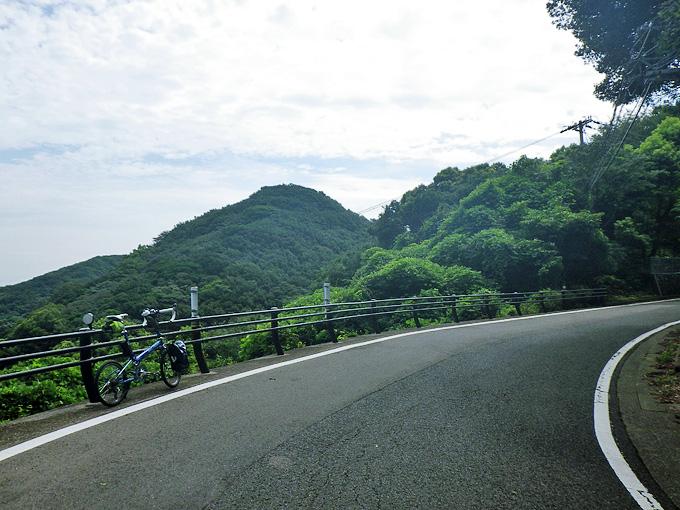淡路島・洲本市南部の山道の風景。曲がりくねった上り坂に、バイクフライデーの折り畳みミニベロ「ニューワールドツーリスト」が停められている写真。