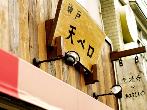 商店街の軒先の赤いテント、その上に「神戸天ペロ」と書かれた看板