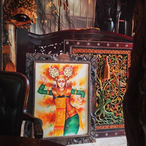 バリラグーンの店内の一角の写真。いろいろなインドネシア雑貨が飾られた店内に、髪や全身にカラフルな飾りを着けた女性が踊っている姿の絵画が置かれている。