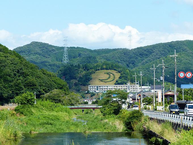 川が流れている。むこうの景色の山の斜面に、大きな「三日月」の絵が見える。植え込みで描かれているようだ。