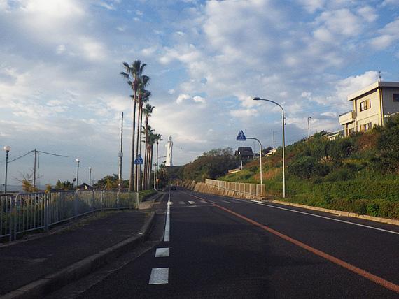 淡路島・仮屋付近の風景。道路脇に椰子の木が立ち並び、むこうには巨大な仏像「世界平和台観音像」が見える。