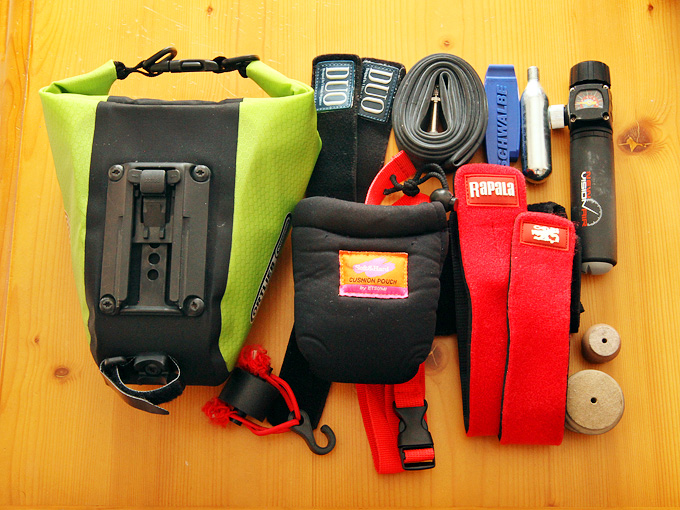 オルトリーブの「サドルバッグM」にどのくらいの量の荷物が入るのかを示した写真。オルトリーブの「サドルバッグM」の横に、携帯用エアーポンプやタイヤチューブ、ベルトなど、たくさんのものが並べられている。