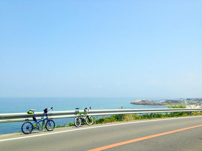断崖の上の道路の白いガードレールに立てかけるようにして、青い自転車「バイクフライデーのニューワールドツーリスト」と、緑色の自転車「ブルーノミニベロ20ロード」が停められている。むこうには雲一つない青空と、遥か下に青い海が見える。
