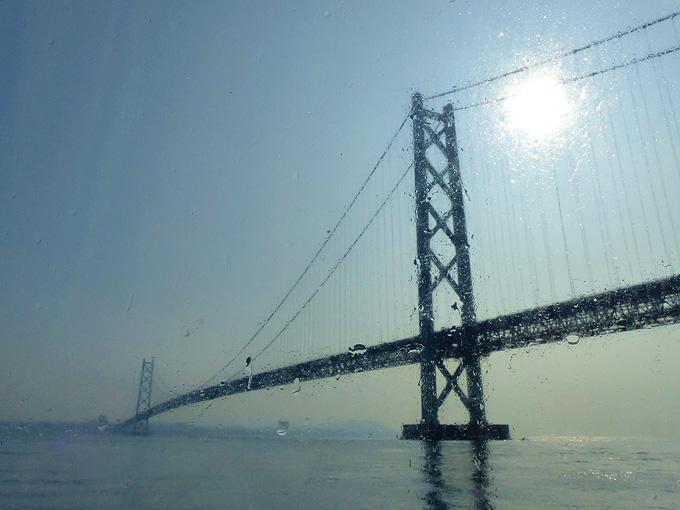 明石と淡路島を結ぶ高速船「淡路ジェノバライン」の船内から見上げる明石海峡大橋の姿。船の窓には波しぶきがかかってキラキラしている。