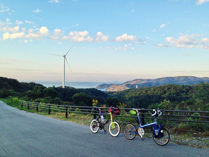 風力発電の巨大な風車の前に2台の自転車、バイクフライデーの折り畳みミニベロ「ニューワールドツーリスト」とミニベロロード「コメットR」が停められている写真。むこうには空が広がっている。