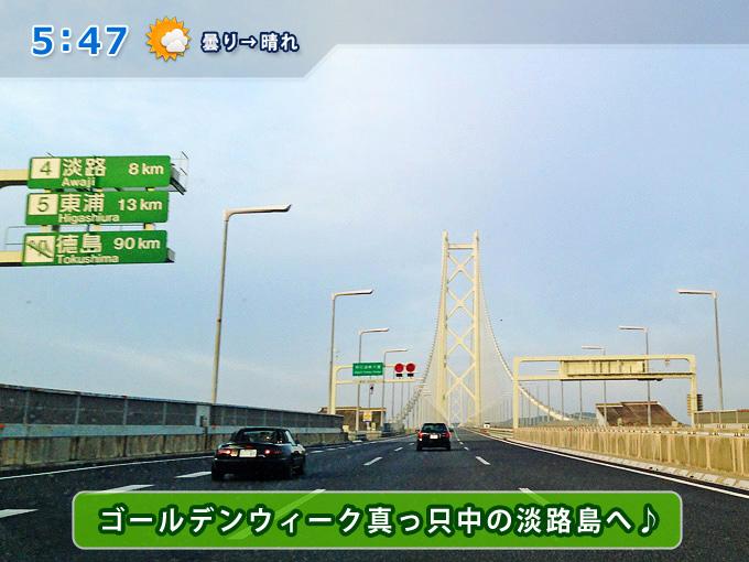 明石海峡大橋を渡る車の中から見た写真。前方に明石海峡大橋の橋脚と淡路島が見える。