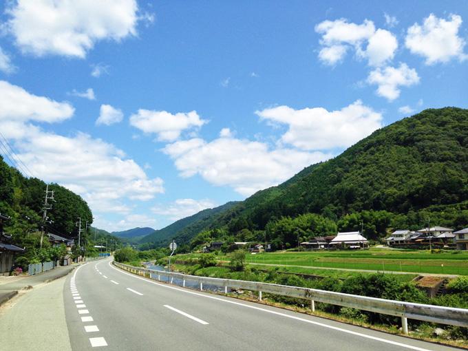 ゆるやかに右に曲がってゆく道路。その脇には川が流れていて、そのむこうには山が見える。