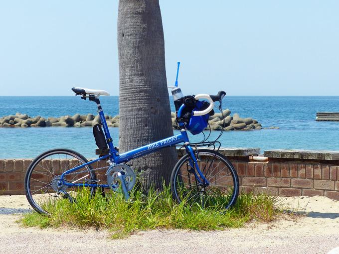 グースネックステムが装着されたバイクフライデー・ニューワールドツーリストが海岸に停められている写真。