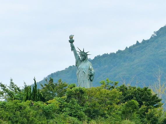 淡路島にある巨大な仏像「世界平和大観音像」の後ろの林の中に立つ「自由の女神像」の写真。木々の中から飛び出すようにして立っている。