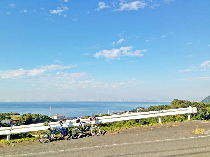 急な坂道の写真。ガードレールの前に2台の自転車、バイクフライデーの折り畳みミニベロ「ニューワールドツーリスト」とミニベロロード「コメットR」が停められている。むこうには海が見える。