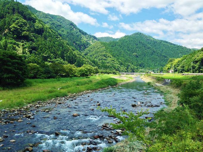清らかな川が、むこうからこちらへ流れている。川の両側は緑色の草むらで、景色のむこうは山が見える。上には青空が広がっている。