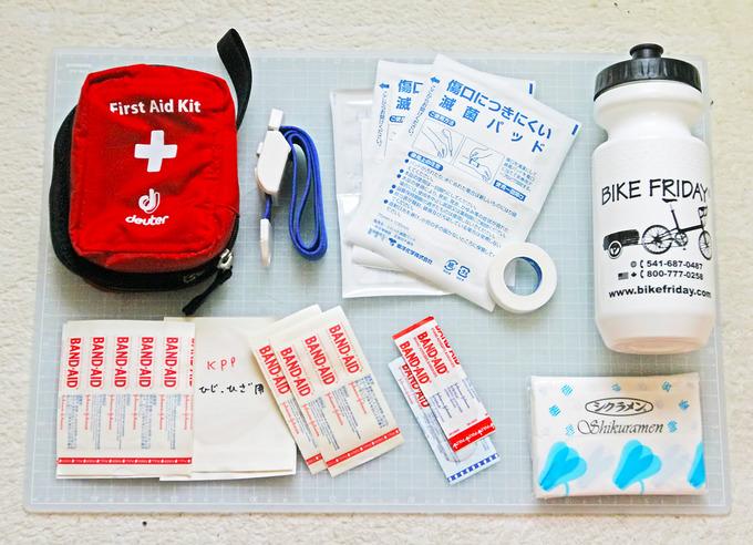 自転車に乗る時のファーストエイド用品を並べた写真。いろいろなものがある。