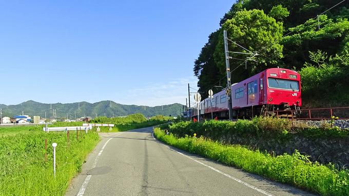 緑いっぱいの田舎の風景の中をJR播但線の赤い電車が走ってゆく写真。