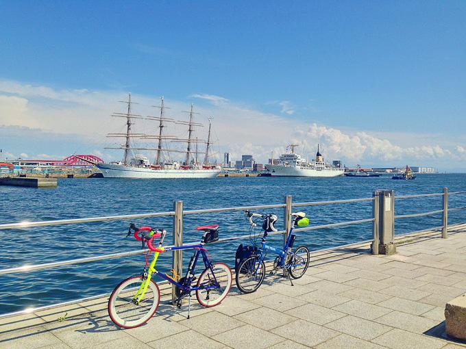 神戸のメリケンパークの一角。青空の下、銀色の柵の向こうは青い海。むこうには大型帆船が停泊している。そんな風景を背景に、折り畳みミニベロ「ニューワールドツーリスト」と、ミニベロロード「コメットR」が停められている写真。