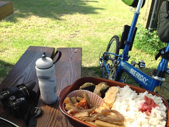 淡路島の「炬口漁港」付近の公園の風景。緑色の芝生広場で、茶色のベンチにカメラや水のボトルが置かれ、手前にはお弁当が見える。すぐ横にはバイクフライデーの折り畳みミニベロ「ニューワールドツーリスト」が停められている。