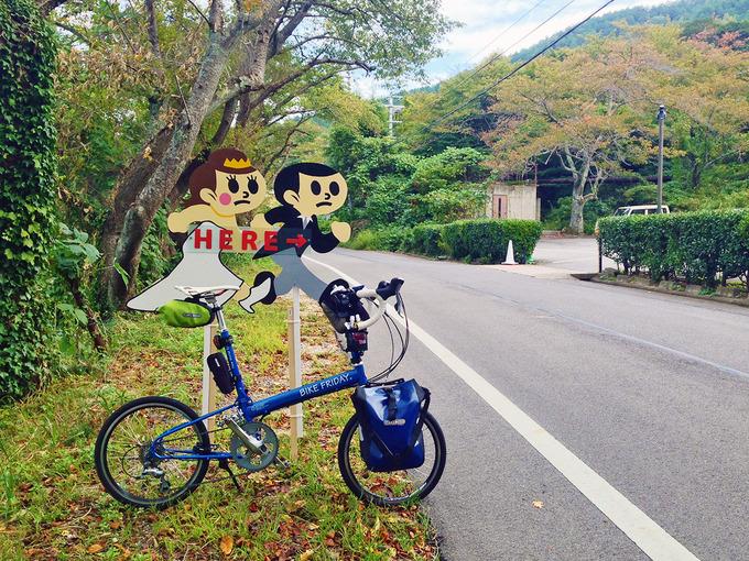 道路沿いに置かれた「新郎・新婦」のイラストの立て看板。近くの結婚式場の場所を示している。その看板の前にバイクフライデーの折り畳みミニベロ「ニューワールドツーリスト」が停められている。
