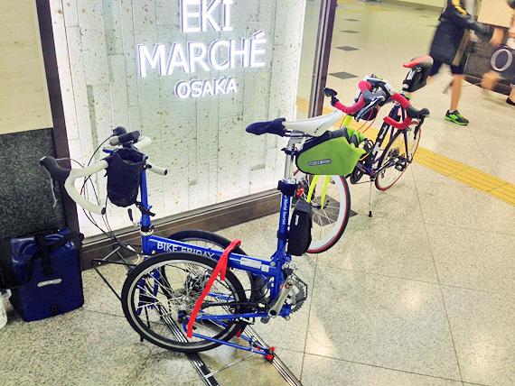 JR大阪駅の構内でバイクフライデーの折り畳みミニベロ「ニューワールドツーリスト」が折り畳まれている最中の写真。となりには友人のミニベロ「コメットR」が停められている。