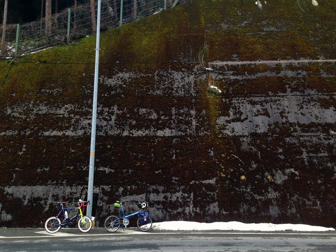 滋賀県大津市の比叡山系の北部「途中口」付近の写真。山側は切り立った高いコンクリートの壁になっていて、壁のところどころに苔が生えている。壁に生えた草や道路脇には雪が積もっている。道路には2台の自転車、「ニューワールドツーリスト」と「コメットR」が停められている。
