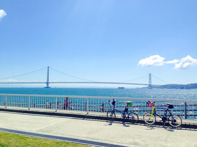 明石市大蔵海岸から見る明石海峡の風景。白い柵の前に2台の自転車、バイクフライデーの折り畳みミニベロ「ニューワールドツーリスト」とフジのミニベロロード「コメットR」が停められている。むこうには青い海、青い空、淡路島と、明石海峡大橋が見える。