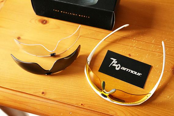白いフレームのサングラスに黄色のレンズが装着されて置かれていて、その横にグレーのレンズと透明のレンズが置かれている。