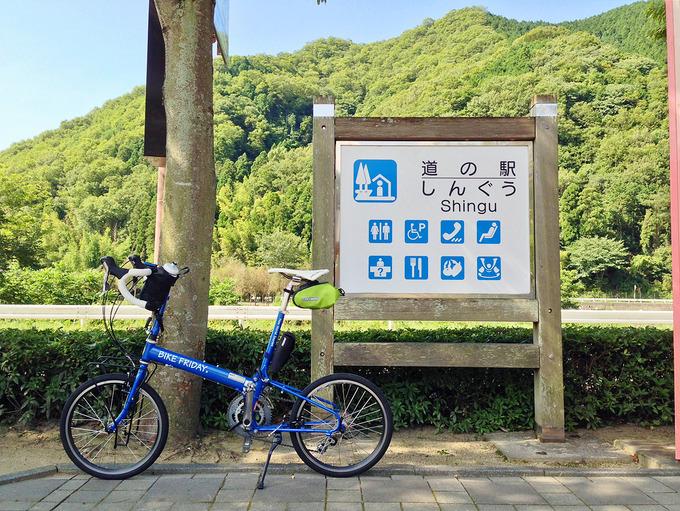 「道の駅しんぐう」と書かれた看板、その横にバイクフライデーの折り畳みミニベロ「ニューワールドツーリスト」。むこうには緑色の木々が見える。