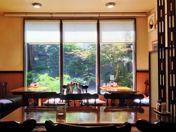 淡路島・福良にある喫茶&とんかつのお店「ママン」の店内の写真。テーブル席が並んでいる。奥には中庭があり、窓越しに緑色の観葉植物などが見える。