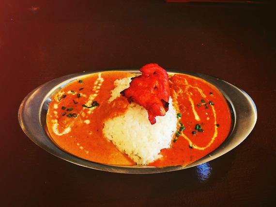 ステンレス製のお皿に盛られたカレーライスの写真。お皿に真ん中にライスが盛り付けられ、その左右にそれぞれ違う色のカレーが入っている。ライスの上には真っ赤なタンドリーチキンが乗っている。