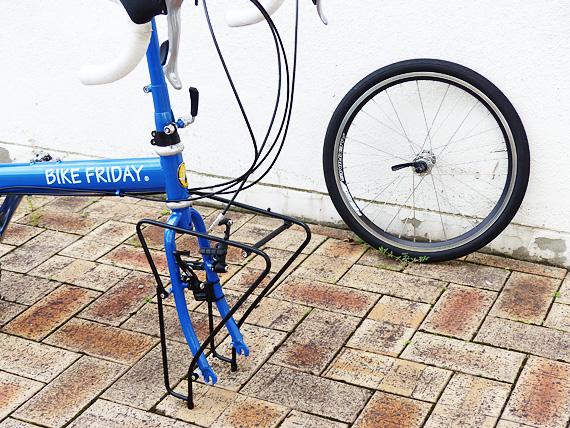 バイクフライデーの折りたたみ小径車「ニューワールドツーリスト」が、前輪が外された状態で自立している写真。フロントキャリアが脚のように地面に接触している。