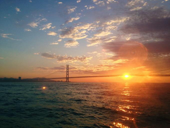 明石海峡の日の出を海上を走るジェノバラインの船内から見た写真。明石海峡大橋のむこうにオレンジ色の朝日が昇って、海面には朝日が反射している。