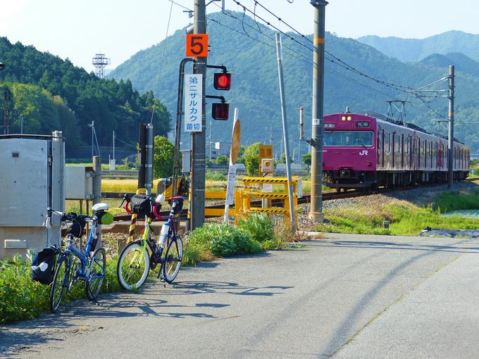 田園風景の中にある鉄道の踏み切り近くに2台の自転車、「ニューワールドツーリスト」と「コメットR」が停められている。むこうからJR播但線の赤い電車が走ってくるのが見える。